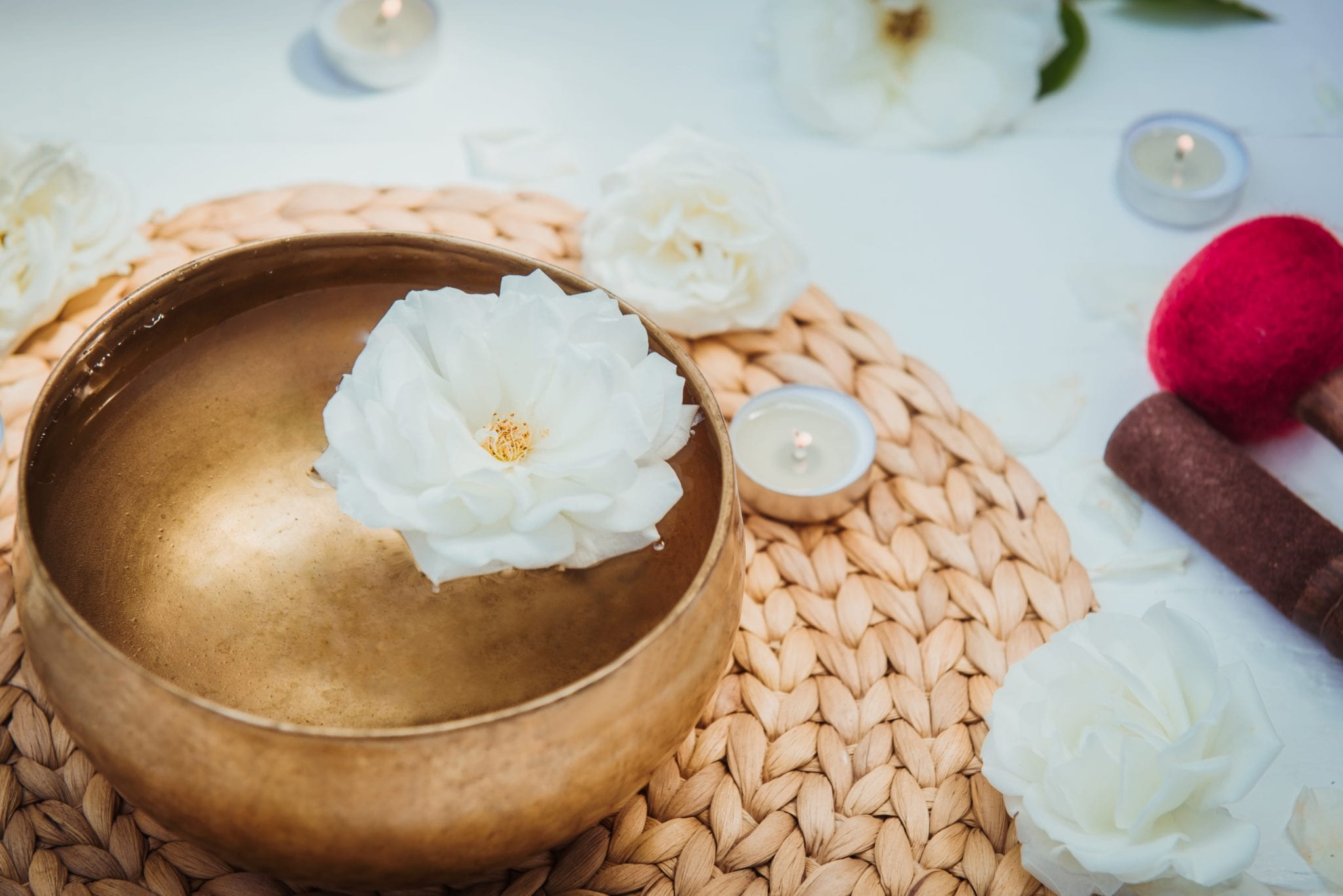 Tibetan singing bowl with floating in water rose inside. Special sticks, burning candles, flowers petals on the white wooden background. Meditation and Relax. Exotic massage. Copy space.
